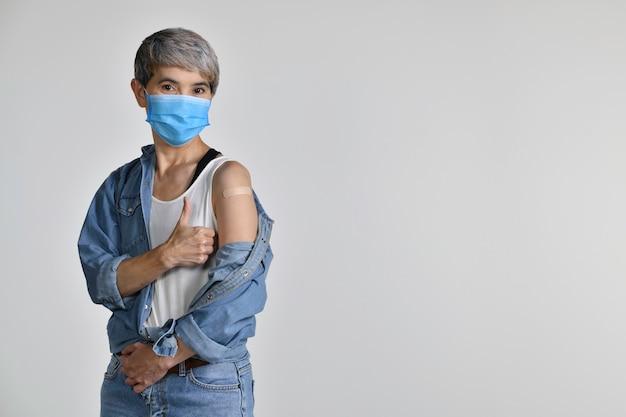 Felice donna asiatica di mezza età vaccinata che mostra i pollici in su alla benda di gesso adesivo sul braccio dopo l'iniezione antivirale di coronavirus isolata su sfondo bianco