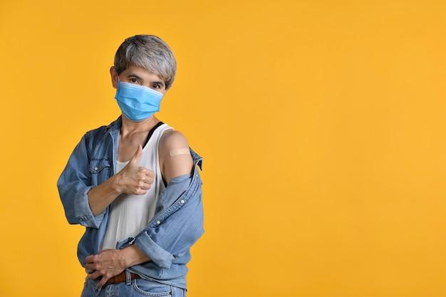 Felice donna asiatica di mezza età vaccinata che mostra i pollici in su alla benda di gesso adesivo sul braccio dopo l'iniezione antivirale di coronavirus isolata su sfondo di colore giallo