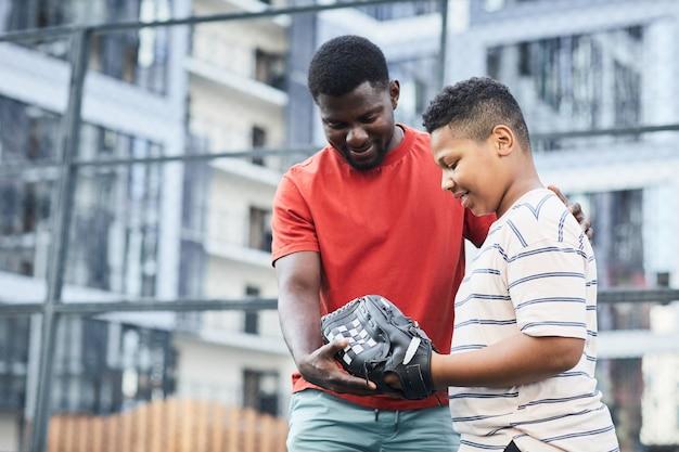 Felice padre nero di mezza età che mostra la posizione della mano mentre insegna al figlio a giocare a baseball