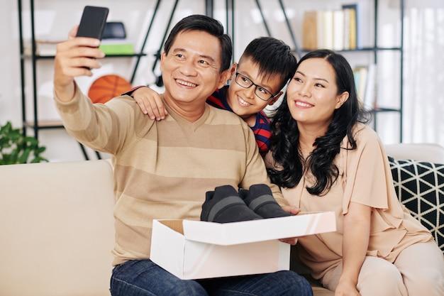 Felice uomo di mezza età che fa foto con moglie sorridente e figlio preadolescente dopo aver ricevuto da loro la scatola con le scarpe nuove