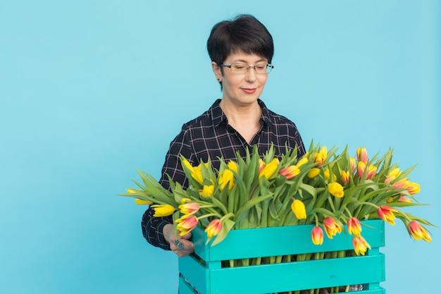 Felice fiorista donna di mezza età con gli occhiali con scatola di tulipani sul blu.
