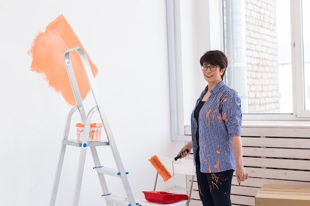 Donna di mezza età felice pittura parete interna con rullo di vernice nella nuova casa. una donna con il rullo