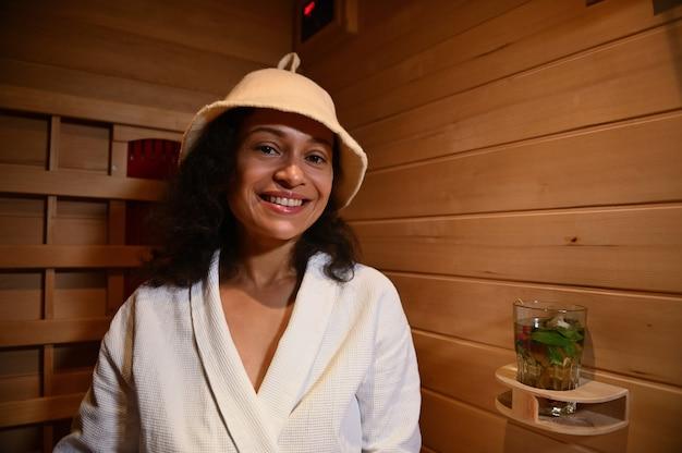 Felice donna di mezza età che sorride mentre si rilassa nella sauna. terapia di bellezza, concetto di cura della pelle e del corpo durante il trattamento del resort termale