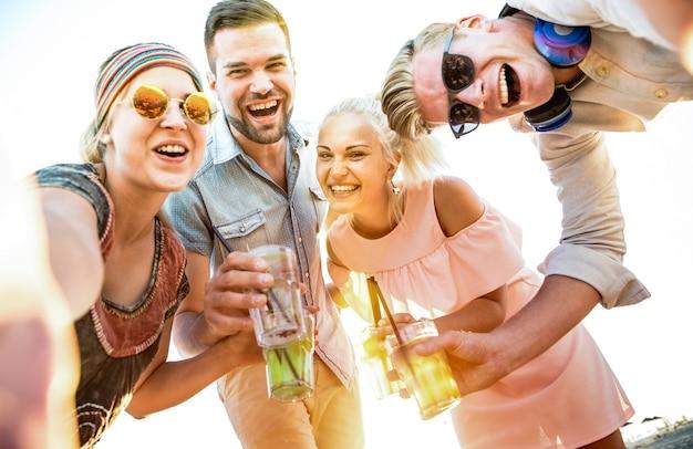 Felice gruppo di amici millenari che si fanno selfie a una divertente festa in spiaggia bevendo cocktail al tramonto