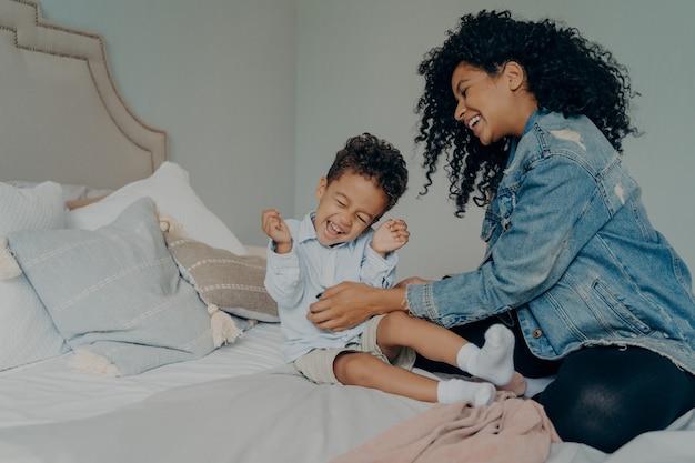 Felice famiglia di razza mista a casa, mamma giovane donna spensierata in giacca di jeans e jeans con i capelli ricci che gioca con il suo dolce bambino, solleticandogli la pancia mentre trascorrono del tempo insieme in camera da letto