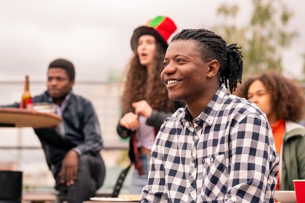 Felice ragazzo di razza mista in camicia a scacchi e i suoi amici che guardano la partita trasmessa all'aperto