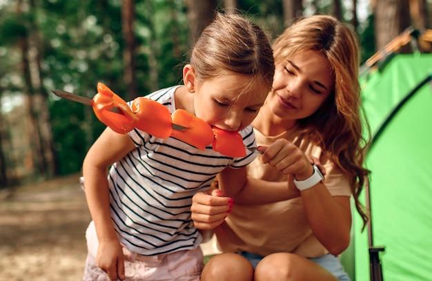 Felice mamma e bambino cucinano pepe sul fuoco durante un picnic. fine settimana in una pineta. campeggio, ricreazione, escursionismo.