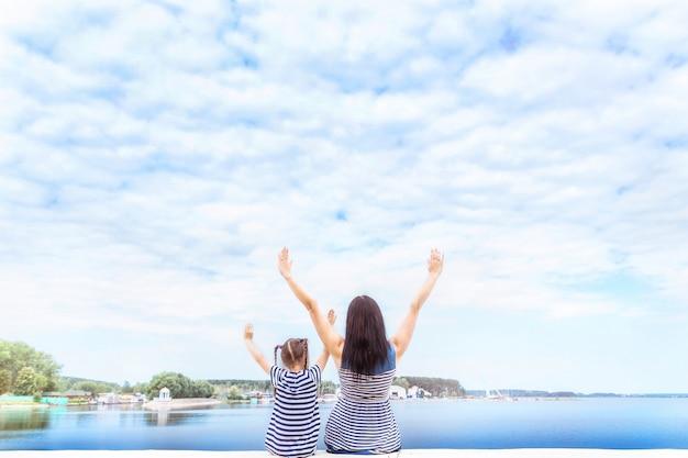 Felice mamma e figlia sono seduti con le mani in alto