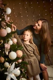 La mamma e la figlia felici decorano l'albero di natale sullo sfondo delle ghirlande