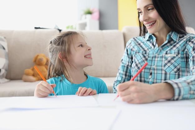 Mamma e figlia felici disegnano con le matite su carta