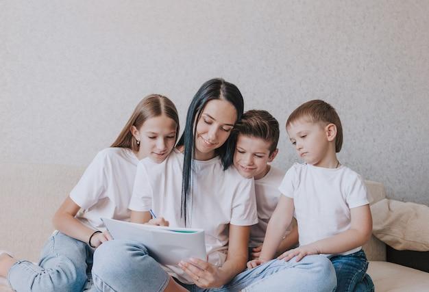 Una mamma felice disegna un'immagine in un album seduta sul divano circondata dai suoi amorevoli figli.
