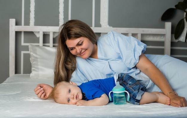 La mamma felice è sdraiata sul letto con un bambino