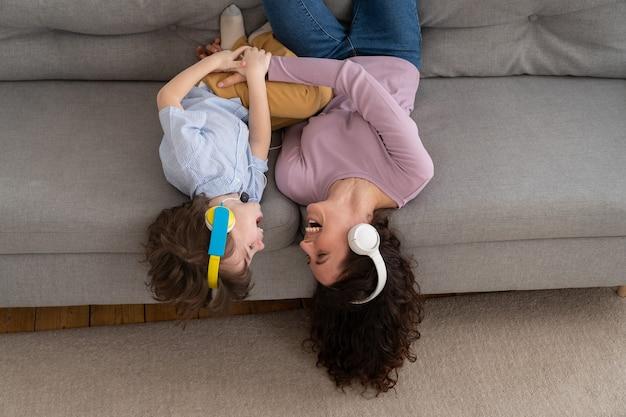 Felice mamma e bambino sdraiato a testa in giù sul divano a casa ridendo solletico vicenda ascoltando musica