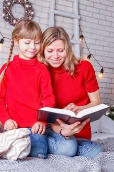 Mamma e bambini felici leggono il libro a casa a natale