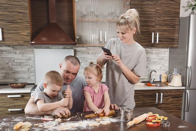 La mamma felice scatta foto di papà con due bambini piccoli in cucina mentre prepara i biscotti di farina. famiglia felice che cucina insieme
