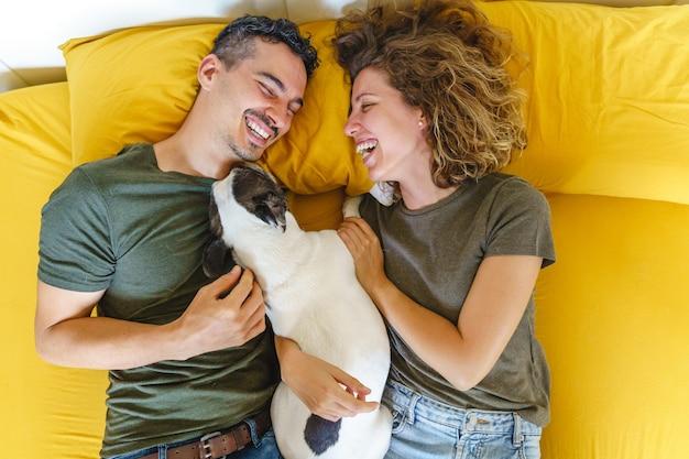 Momento felice di coppia con animali domestici a casa sul letto. vista dall'alto orizzontale che gioca con l'animale domestico all'interno.