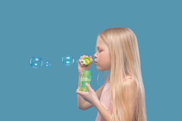 Momento felice. bambina sveglia con capelli biondi lunghi che stanno lateralmente facendo le bolle di sapone su fondo blu nella foto dello studio