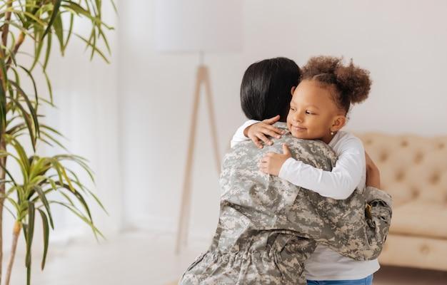 Momento felice. adorabile e appassionata madre aggraziata e sua figlia carina che si abbracciano strettamente e sembrano felici di rivedersi