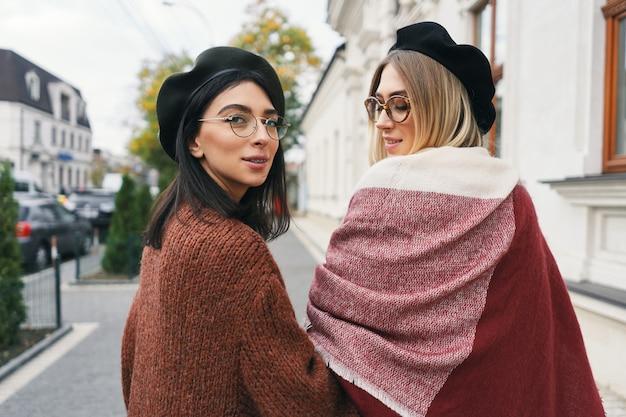Momenti felici con due ragazze alla moda, guardando sopra la spalla, sorridendo, camminando per una strada della città. ritratto del primo piano, giovani donne attraenti divertenti e gioiose che hanno divertimento, migliori amici, sorelle.