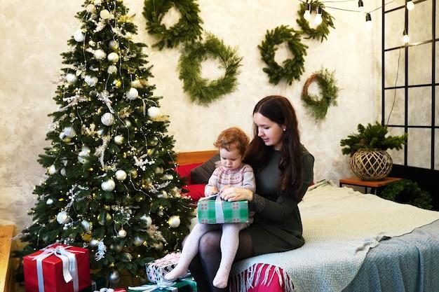 Madre felice e neonata che tengono il contenitore di regalo di natale a casa