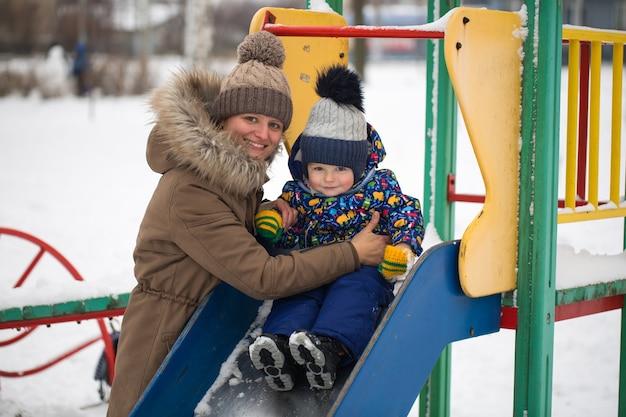 Felice madre e bambino nel parco invernale. famiglia all'aperto. mamma allegra con il suo bambino