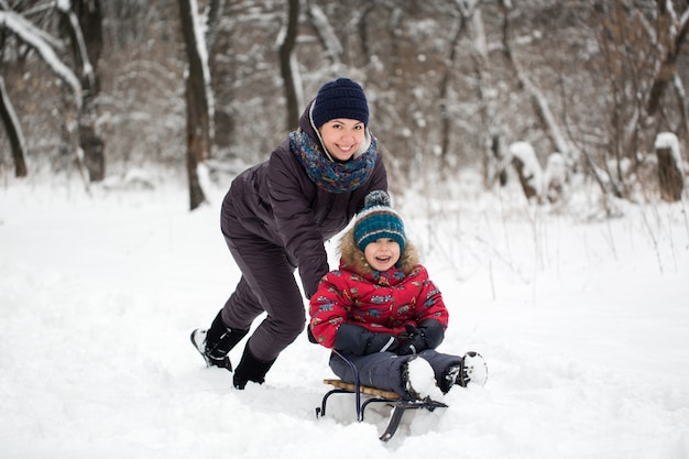 Madre e bambino felici nel parco di inverno