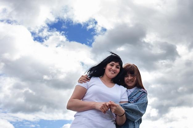La madre e la figlia felici contro il cielo