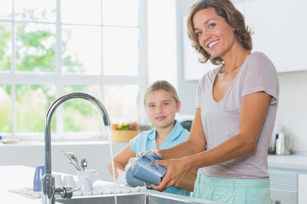 Felice madre e figlia facendo il bucato