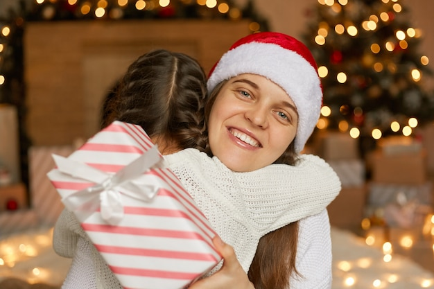 Madre felice e figlia che si danno il regalo di natale a vicenda e che si abbracciano, mamma che indossa il cappello della santa e sorridente, famiglia in posa a casa nella stanza festiva.