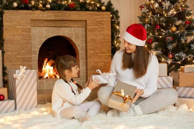 Felice madre e figlia che si danno il regalo di natale a vicenda, trascorrono insieme la vigilia di capodanno, in posa nel soggiorno festivo, seduti sul pavimento vicino al camino e all'albero di natale.