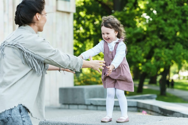 Madre e figlia felici che giocano su una strada