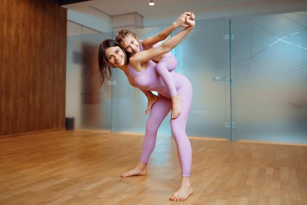 Felice madre e figlia pone in palestra, allenamento yoga. mamma e bambina in abiti sportivi, donna con bambino in formazione congiunta in club sportivo