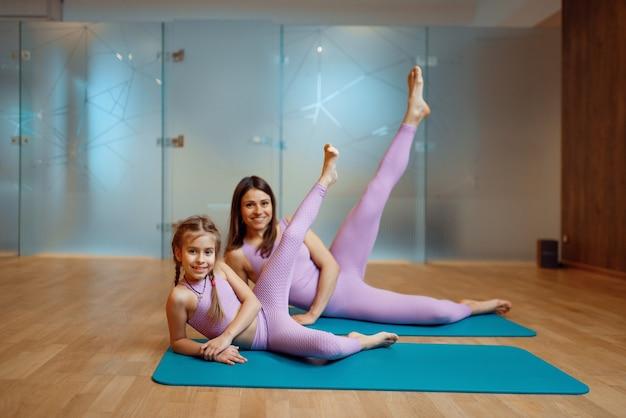 Felice madre e figlia pone sulle stuoie in palestra, allenamento yoga. mamma e bambina in abiti sportivi, donna con bambino in formazione congiunta in club sportivo