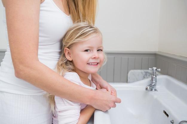Madre felice e figlia che lavano le mani