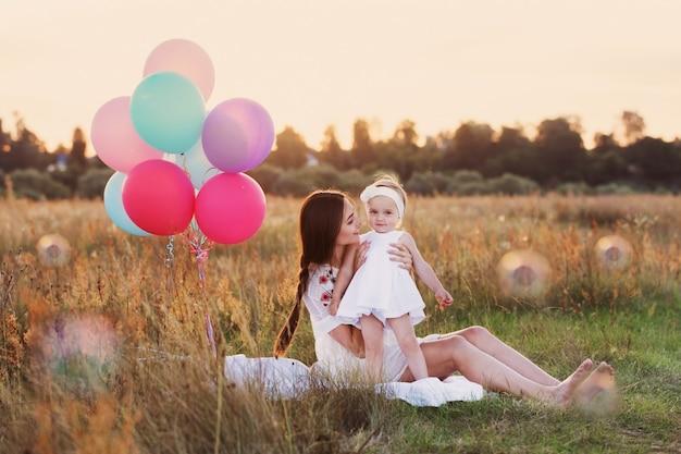 Felice madre e figlia con palloncini all'aperto