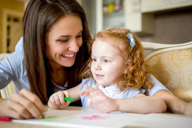 Felice madre disegnando con piccola figlia di redhead