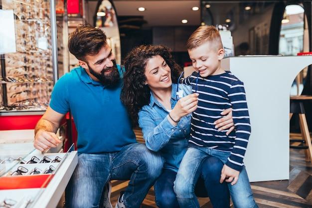 Felice madre e padre che scelgono la montatura degli occhiali per il figlio in un negozio di ottica.