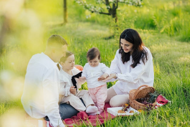 Madre e padre felici che giocano con i bambini nella natura