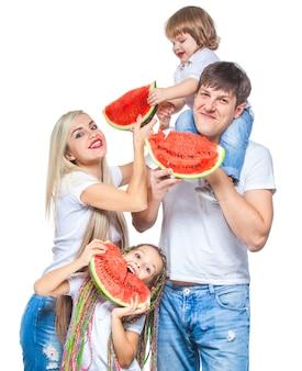 Felice madre, padre e figlia in piedi con pezzi di anguria