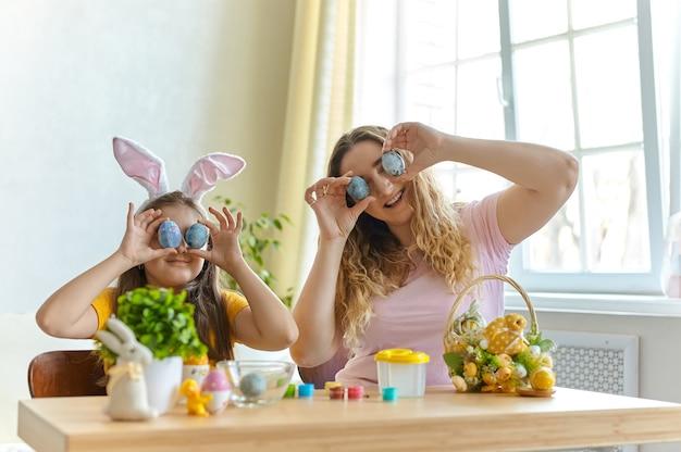 Madre felice e sua figlia che tengono le uova di pasqua per chiudere gli occhi per la celebrazione del giorno di pasqua, sono nel soggiorno alla soleggiata giornata di primavera con la faccia sorridente