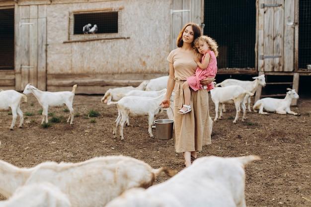 Felice madre e sua figlia trascorrono del tempo in una fattoria ecologica tra le capre.