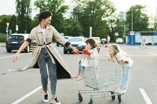La madre felice e le sue figlie si divertono con un carrello della spesa