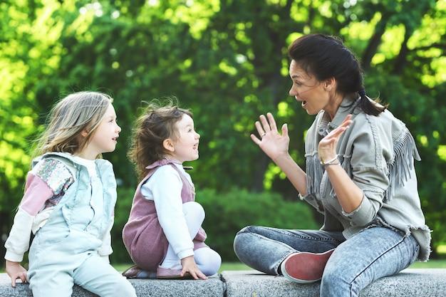 Madre felice e le sue due figlie sedute e giocando in un parco cittadino