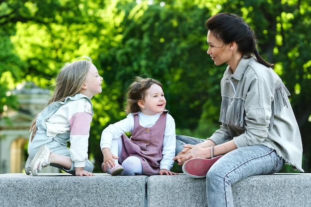 Madre felice e le sue due figlie che si siedono e giocano in una città