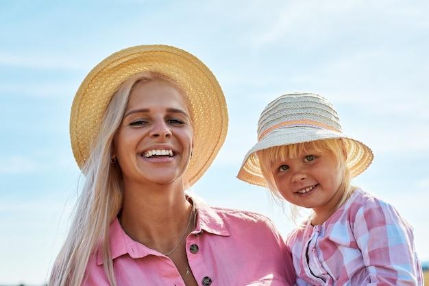 Felice madre che tiene bambino sorridente su un campo di grano alla luce del sole.