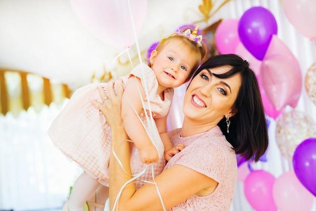 La madre felice tiene la figlia sulle mani sullo sfondo di molti palloni gonfiabili