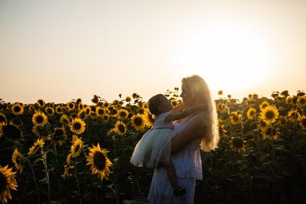 La madre felice abbraccia sua figlia in un campo di girasoli, vestiti bianchi