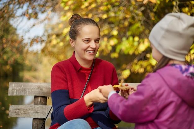 Madre felice e bambino che tengono le foglie gialle di autunno all'aperto