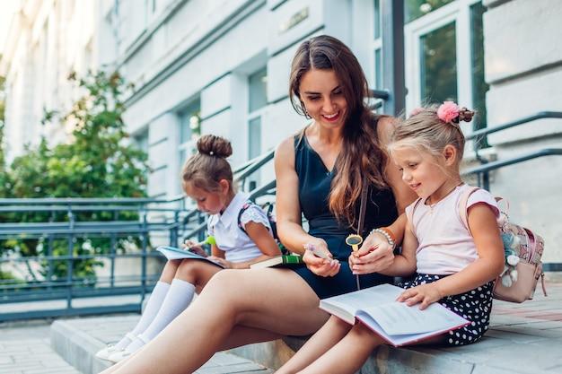 Le figlie felici della madre e dei bambini trascorrono del tempo insieme dopo le lezioni. bambini che leggono libri che fanno i compiti all'aperto della scuola primaria.