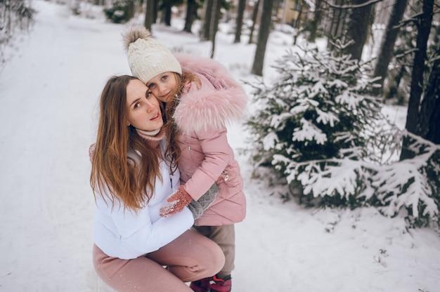 Madre felice e bambina carina in outwear caldo rosa camminare divertendosi e abbracciando nella foresta di conifere inverno freddo bianco nevoso con boschi di abete rosso all'aperto